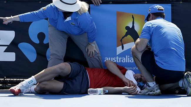 Frank Dancevic of Canada lies on the court after collapsing.