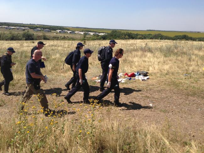Searching for remains ... Australian Federal Police at the MH17 crash site in Ukraine. Chicken sheds can be seen in the background. Picture: Paul Toohey