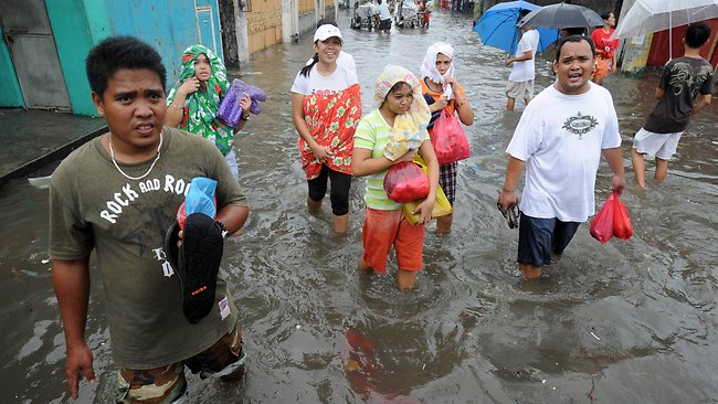 Residents wade through a flooded street in the town of Navotas in suburban Manila. AFP PHOTO