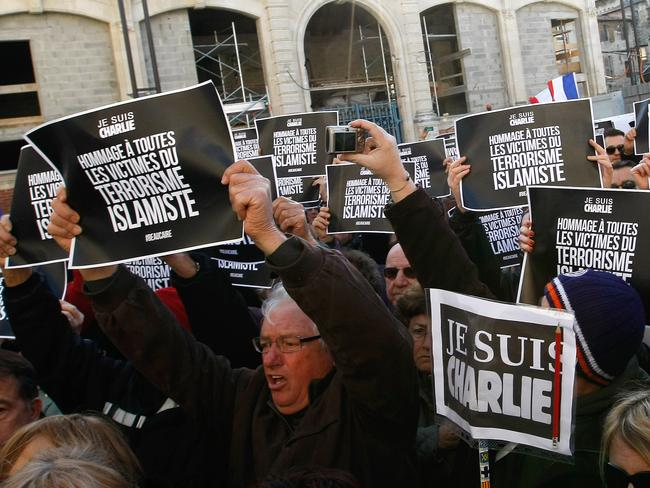 "National Front leaders hold placards reading 'I am Charlie' in contrast to the slogan from the party's former leader, Jean-Marie Le Pen who said ""I am not Charlie' via video. Picture: AP Photo/Claude Paris."