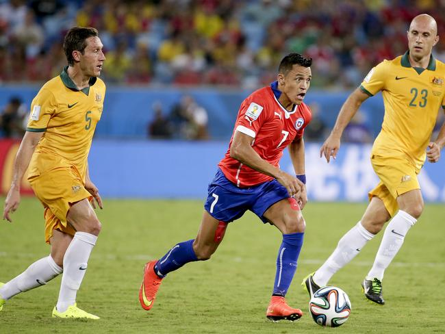 Injuries ... Chile's Alexis Sanchez, centre, runs between Australia's Mark Milligan, left, and Mark Bresciano.
