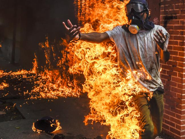 A demonstrator catches fire, after the gas tank of a police motorbike exploded, during clashes in a protest against Venezuelan President Nicolas Maduro, in Caracas last month. Picture: Juan Barreto/AFP
