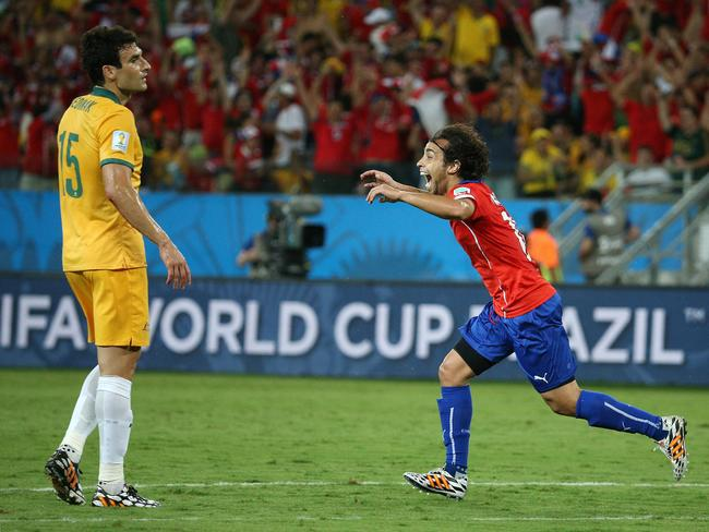 Australia's Mile Jedinak looks on as Jorge Valdivia of Chile scores the second goal.