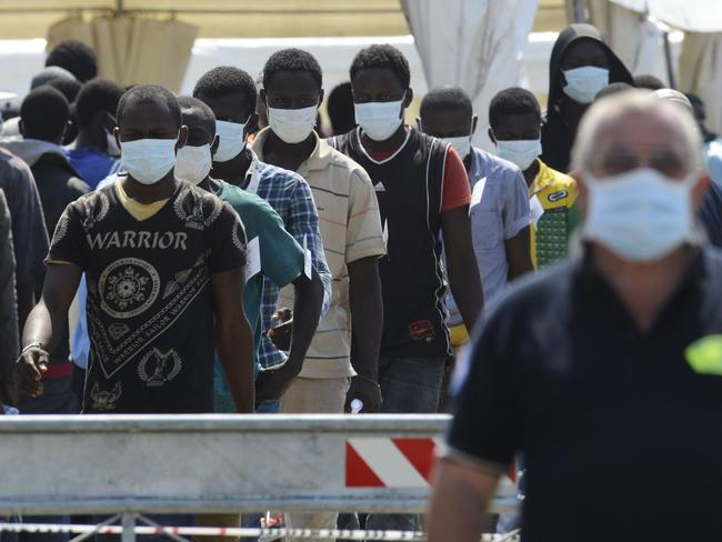 Migrants disembark from an Italian military ship.