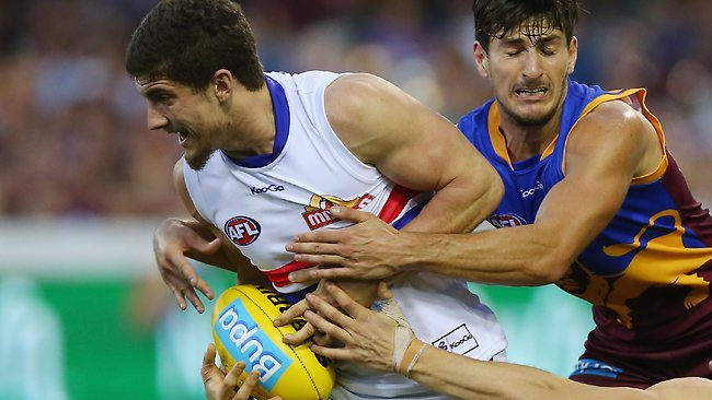 DO NOT ARCHIVE... 25/08/2013 WIRE: BRISBANE, AUSTRALIA - AUGUST 25: Tom Liberatore of the Bulldogs is tackled by Sam Mayes of the Lions during the round 22 AFL match between the Brisbane Lions and the Western Bulldogs at The Gabba on August 25, 2013 in Brisbane, Australia. (Photo by Chris Hyde/Getty Images) Pic. Images Getty