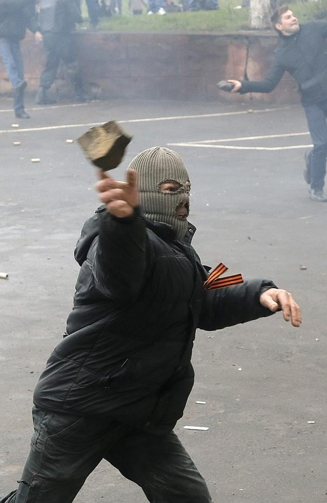 Pro-Russian men throw stones during the mass storming of a police station in Horlivka, eastern Ukraine.