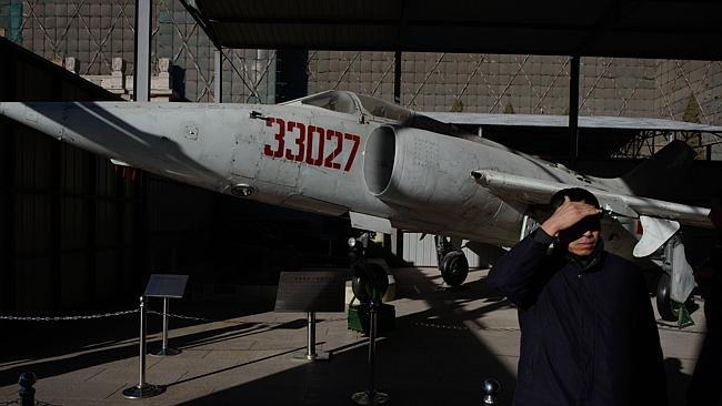 A visitor stands before a decommissioned Chinese A-5 Ground Attack aircraft at the Military Museum in Beijing. Japan and Sout...