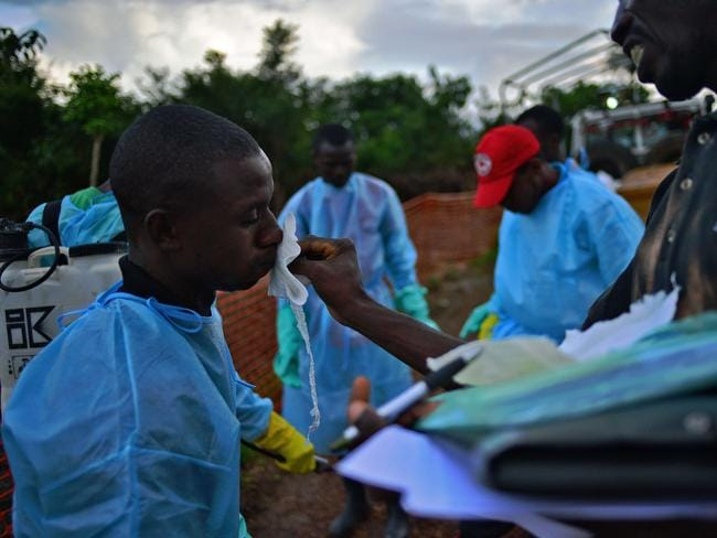 Frontline workers ... Sierra Leonese government burial team members are disinfected after loading the bodies of Ebola victims onto a truck at the Medicins Sans Frontieres (MSF) facility in Kailahun. Picture: Carl de Souza