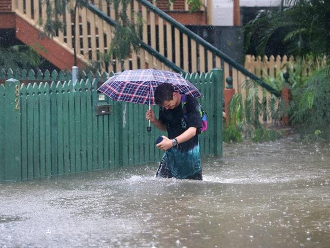 Rigby Wilshire wades through flood waters to get to his home on Longlands st at East Brisbane. Picture: Darren England.