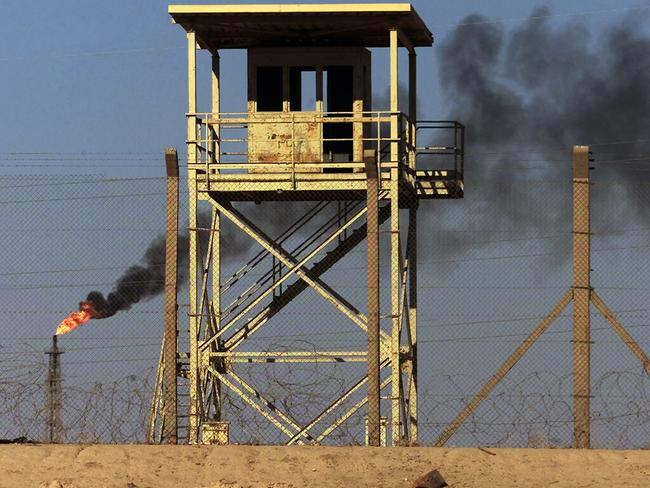 Attacked ... An abandoned watchtower and lines of barbed wire are seen surrounding Iraq's largest oil refinery as smoke rises from a petroleum gas flare, in the city of Beiji, north of Baghdad.