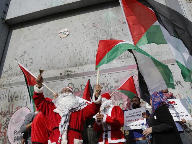 Palestinians dressed as Santa Claus wave national flags in front of the Israeli separation barrier during a protest in Bethlehem. Picture: AP/Nasser Shiyoukhi