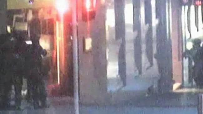 This image from CCTV footage of the Lindt Cafe Siege shows hostage Louisa Hope standing in the middle of the stronghold, illuminated in the explosions as police stormed the building. Picture: Supplied