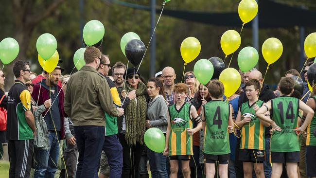 Mo, Evie and Otis Maslin's parents Anthony Maslin (left, red coat black hat) and Rin Norris (centre green scarf, black hat) release balloons to honour their children at a junior football match yesterday. Picture: Will Russell