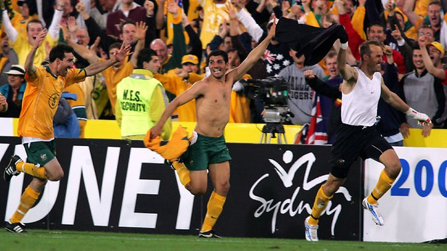 John Aloisi (centre), with Mark Schwarzer (right) lead the charge after Aloisi put the Socceroos into the 2006 World Cup.