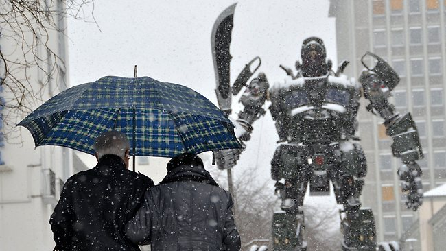 A couple passes the sculpture 'Transformer' by Chinese artist Bi Heng during snowfall in Kassel, central Germany. Picture: AP