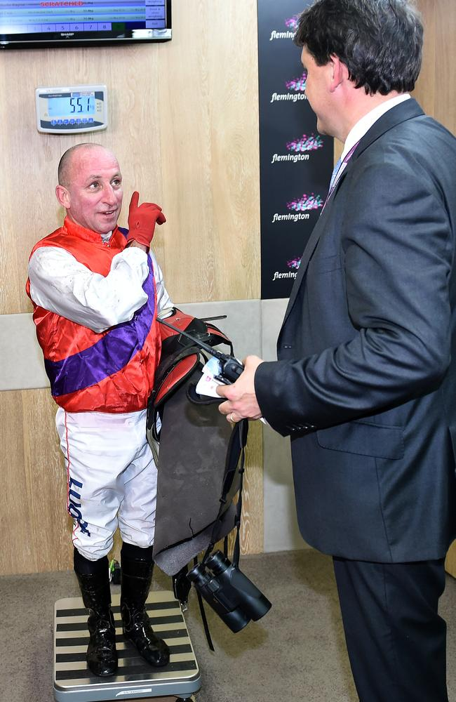 Jim Cassidy weighs under the watch of chief steward Terry Bailey for the last time on Oaks Day at Flemington.