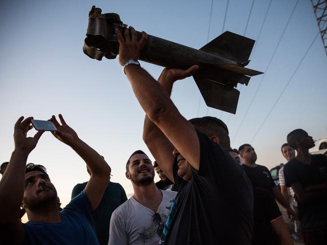 A man holds up a destroyed rocket, which he says was fired from inside Gaza towards Israel, for a crowd watching the Israeli attacks from Sderot. Picture: Andrew Burton/Getty Images