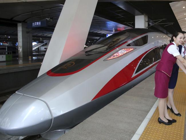 FILE - In this June 26, 2017 file photo, railway workers pose for photos with the Fuxing, China's latest high speed train capable of reaching 400kph (248mph) during its maiden service from Beijing. China is relaunching the world's fastest bullet trains in September 2017, running at 350 kilometers (217 miles) per hour. China first ran trains at 350 kilometers per hour in August 2008, but cut speeds back to 250-300 kilometer per hour in 2011 following a two-train collision near the city of Wenzhou that killed 40 people and injured 191. (Chinatopix Via AP, File)