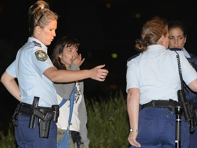 Police talk to a woman at the scene. Picture: Gordon Mccomiskie