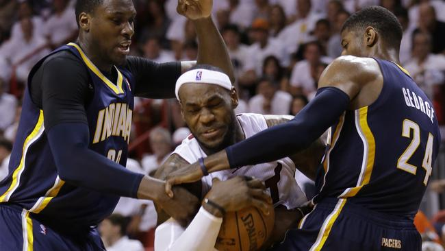 Indiana Pacers centre Ian Mahinmi, left, and forward Paul George (24) attempt to block Miami Heat forward LeBron James during the second half of Game 4 in the NBA basketball Eastern Conference finals playoff series, Monday, May 26, 2014, in Miami. (AP Photo/Wilfredo Lee)
