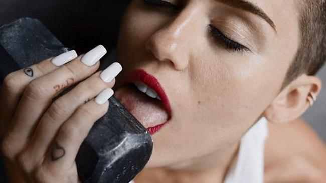"Miley Cyrus licking a sledgehammer in her new ""Wrecking Ball"" music video."