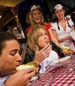 TV personality Charlotte Dawson beats Kyle Linahan in a Virgin Mobile pie-eating contest at Harry's Cafe De Wheels, Woolloomooloo in Sydney.