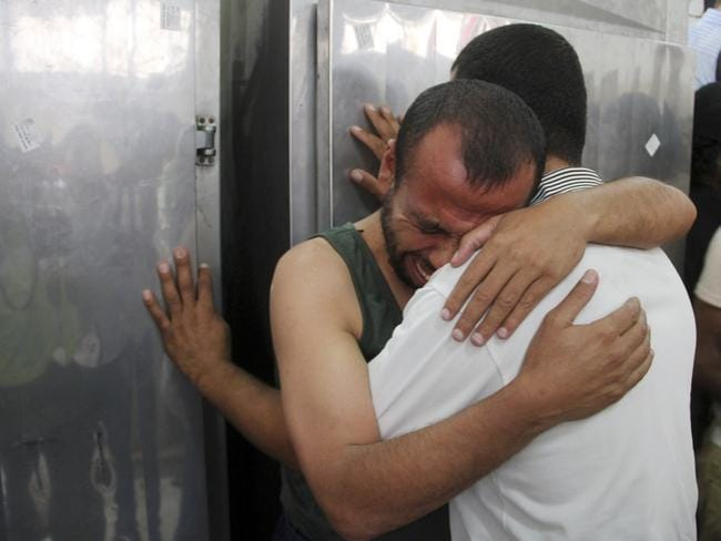 Grief-stricken ... Palestinians comfort each other at the morgue of al Najar hospital as one of their relatives was killed in an Israeli air strike on their family house in Gaza.