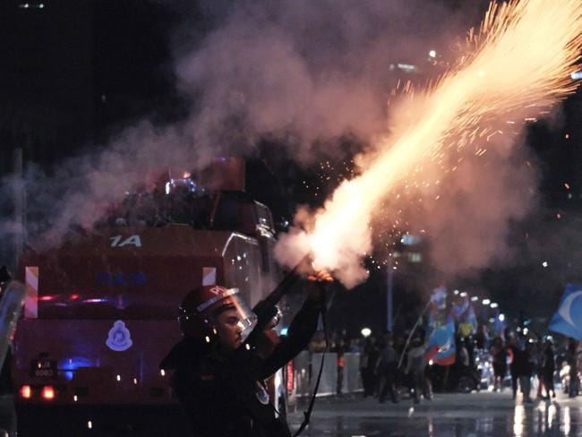 A Malaysian police officer fires tear gas towards opposition party supporters in Putrajaya, Malaysia. Picture: AP