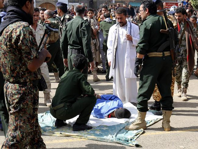 A doctors stands close to    Yemeni security forces preparing to execute Mohammed al-Moghrabi. Picture: AFP