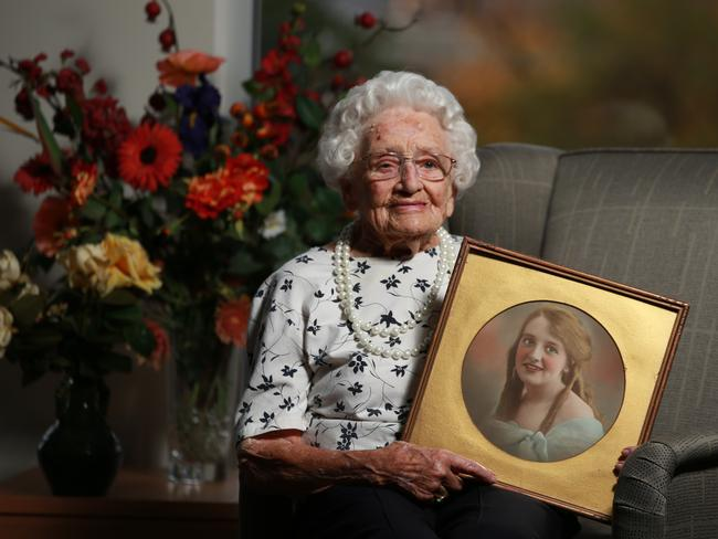 Irene Harris, who is 106, holds a portrait of her taken in 1925 — when she was 17.