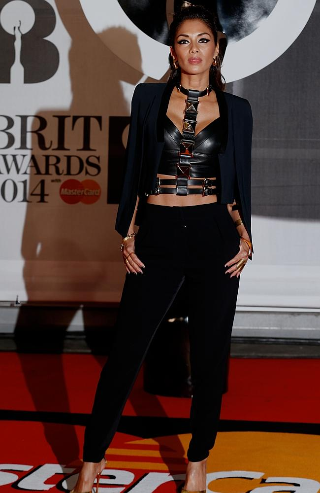 US singer and television personality Nicole Scherzinger poses on the red carpet arriving at the BRIT Awards 2014.