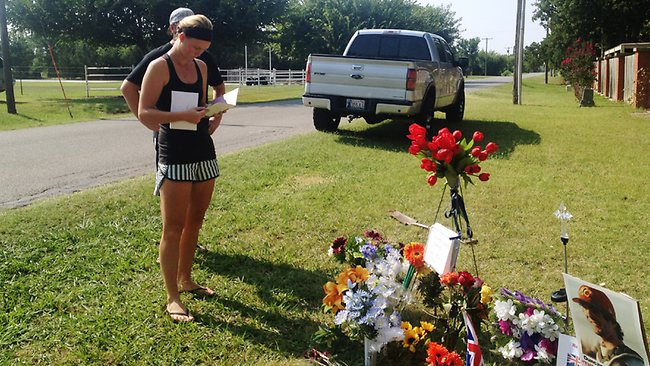 Sarah Harper, Christopher Lane's girlfriend, stands beside a memorial along the road where police say Lane, an Australian baseball player was shot and killed on Friday, August 16 by three bored teenagers who decided to kill someone for fun, in Duncan, Oklahoma.