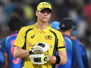 Australia's captian Steve Smith (C) reacts as Indian cricketers celebrate the wicket of Australia's Travis Head during the second one day international (ODI) match of the ongoing India-Australia cricket series at the Eden Gardens Cricket Stadium in Kolkata on September 21, 2017. / AFP PHOTO / Dibyangshu SARKAR / ----IMAGE RESTRICTED TO EDITORIAL USE - STRICTLY NO COMMERCIAL USE----- / GETTYOUT