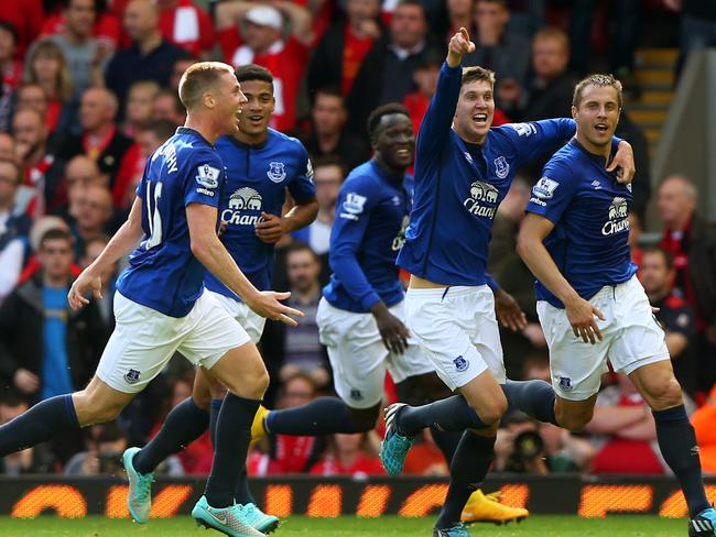 Phil Jagielka is swamped by his teammates after his last-minute heroics.