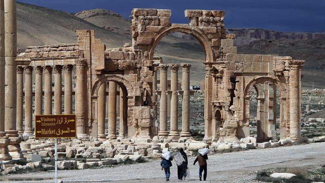 Syrian citizens walk in the ancient oasis city of Palmyra, an archaeological treasure that was declared a UNESCO world heritage site in 1980. Picture: AFP/Joseph Eid