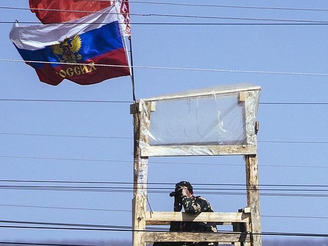 Looking out ... A pro-Russian activist stands guard at a watchtower outside the secret se