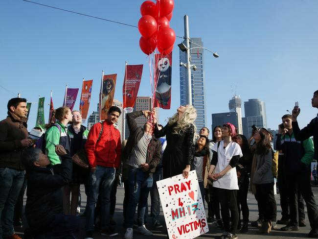 Gabi Grecko releases a small number of red balloons at Federation Square in Melbourne. Picture: Splash News
