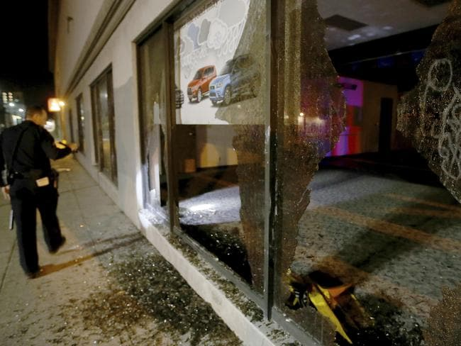 An Oakland police officer checks out damage after a window was broken by protesters. Picture: Jane Tyska/Bay Area News Group via AP