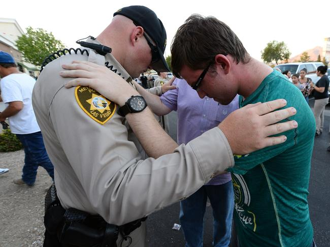 Grief ... Las Vegas Metropolitan Police Department Officer Harrison Porter prays with Ryan Rasmussen of Nevada during a vigil outside CiCi's Pizza. Picture: AFP