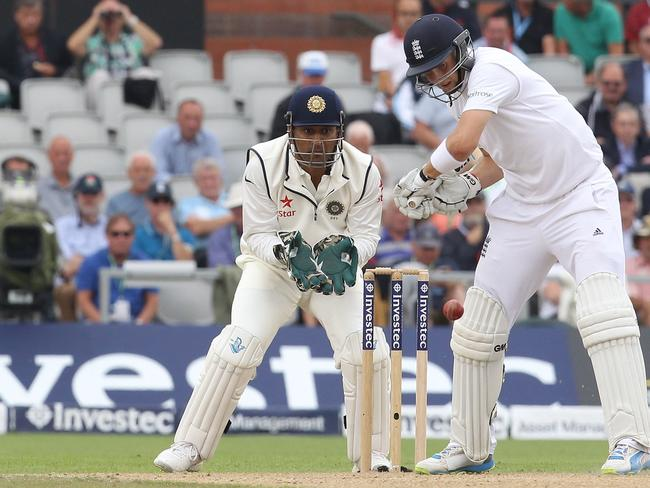 Washed out ... India captain Mahendra Singh Dhoni (L) looks on as England's Joe Root plays a shot.