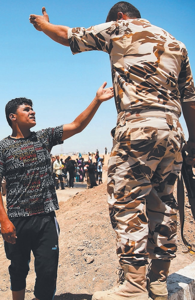 Pushed too far ... An Iraqi man argues with a soldier as Iraqis who have fled recent fighting in the cities of Mosul and Tal Afar try to enter a temporary displacement camp.