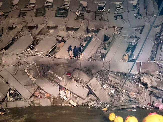 Damage ... rescuers try to enter an office building that collapsed on its side after an early morning earthquake in Tainan. Picture: Supplied