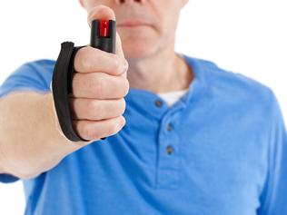 Close-up of a man using mace pepper spray. From iStock