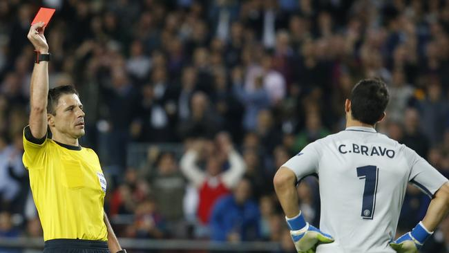 Referee shows a red card to Manchester City's Chilean goalkeeper Claudio Bravo (R).