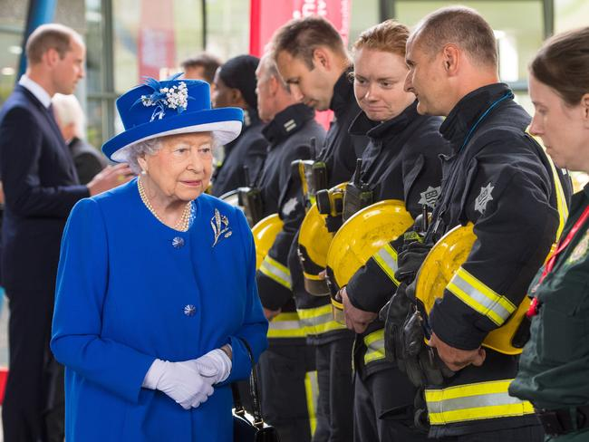 Queen Elizabeth II meets firefighters and paramedics during a visit to the Westway Sports Centre which is providing temporary shelter for those who have been made homeless in the disaster. Picture: Getty