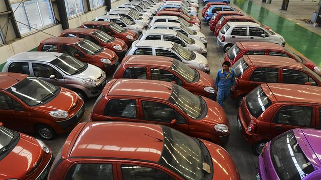 Car giant ... a worker walks among electric cars in a factory in Zouping county, in eastern China.
