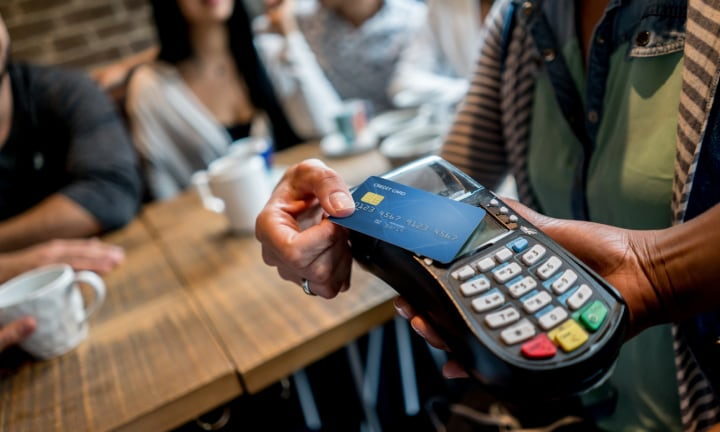 Unrecognizable person making a contactless payment at a restaurant with a credit card. Design on credit card is own design.