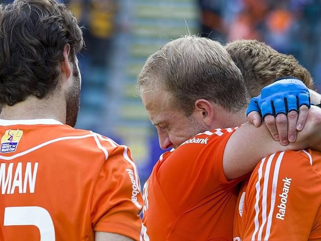 Billy Bakker (C) from the Netherlands reacts with a teammate after losing their men's Field Hockey World Cup game against Australia.