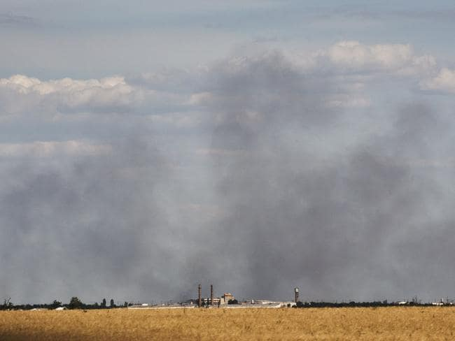 Smoke rises ... moments after the bodies of more than 200 victims of MH17 left in full refrigerated carriages from Torez train station, jet fighters bombed a revered war monument. Picture: Ella Pellegrini