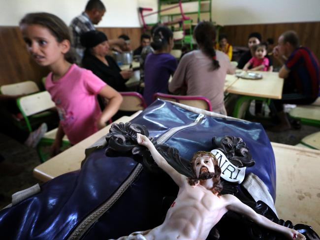 Suffering for their faith ... A statue of Jesus Christ is seen on the bag of an Iraqi Christian who fled the violence in the village of Qaraqush, about 30 kilometres east of the northern province of Nineveh. Source: AFP